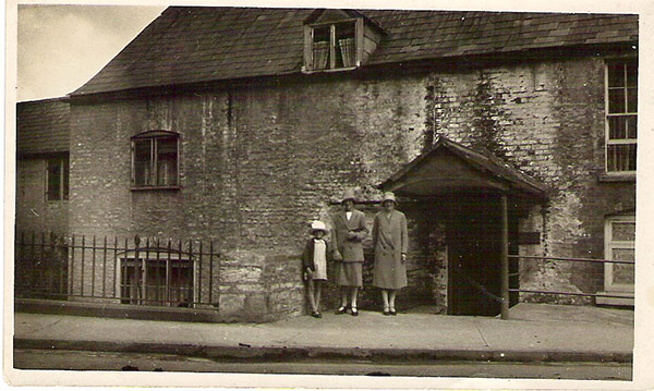 Two women and a little girl stand outside a house that looks very old. Part of the house is below road level.