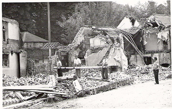 Three men appear to be moving a ladder or plank of wood in the middle of the site where the former Ship Inn cottages are hanging, partially demolished in the background.