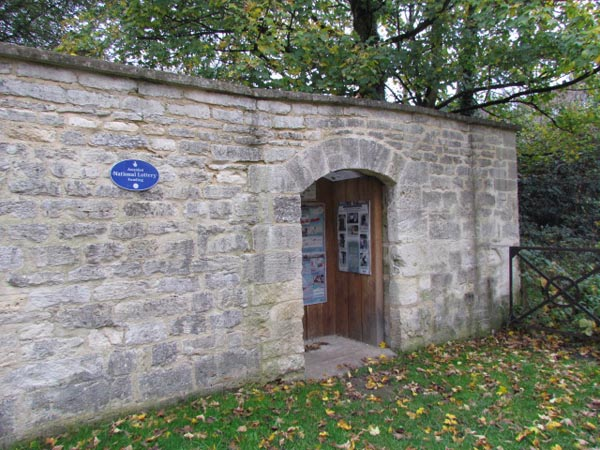 A small stone entrance to allow a man and a horse to get through. A heritage lottery sign on the wall commemorates work to restore the wall.