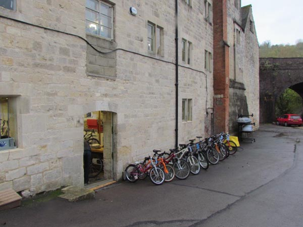One of the restored mill buildings with a row of bikes lined up next to the wall.