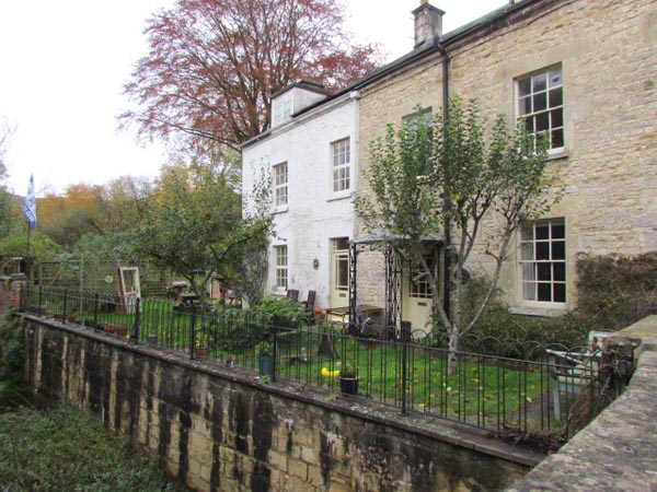 Two stone cottages, built alongside the River Frome, which flows at a lower level under the nearby bridge out of the port.
