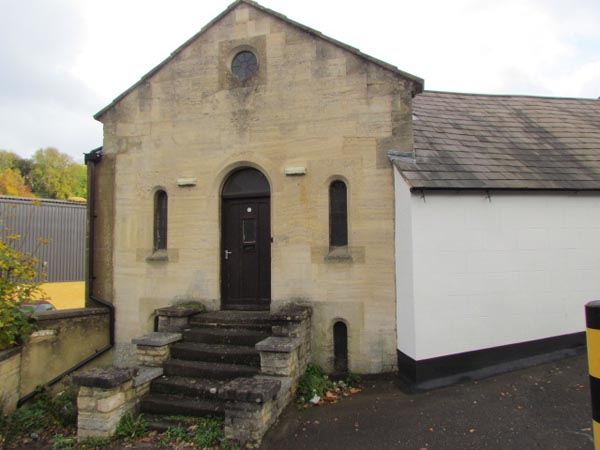 A small, plain, stone chapel with an arched door and narrow windows either side. There is a round window above the door.