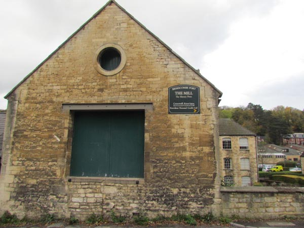 A stone building has central double loading doors and a higher circular opening with its own wooden door behind. Behind it, the main Port Mill building can be seen.