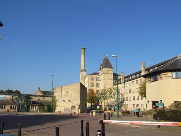 Ebley Mill was cleaned as part of Stroud District Council's restoration scheme and is pale yellow against a blue sky.
