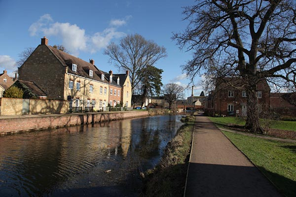 A view along the canal on a sunny winter's day. Houses alongside the waterway are modern, but reflect local building styles.