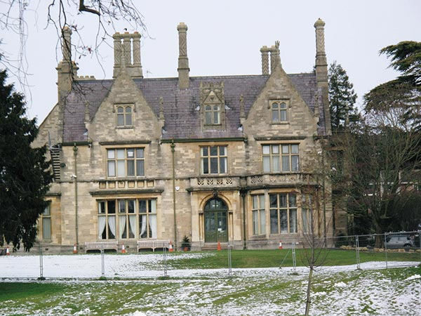 An elegant stone manor, with tall chimneys and stone window surrounds.