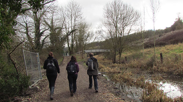This view shows three walkers striding out on the towpath. The canal is quite overgrown at this location, but water can be seen.