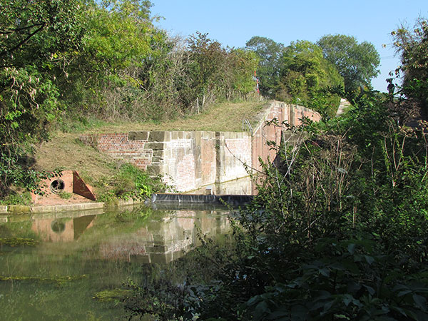 The lock is seen from further away and at a low level. Water flows over a small  weir at the bottom of the lock.