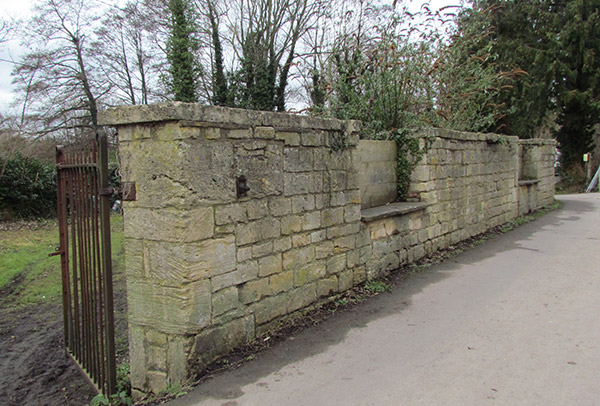 A heavy Cotswold stone wall with a gate made of iron railings next to the towpath.