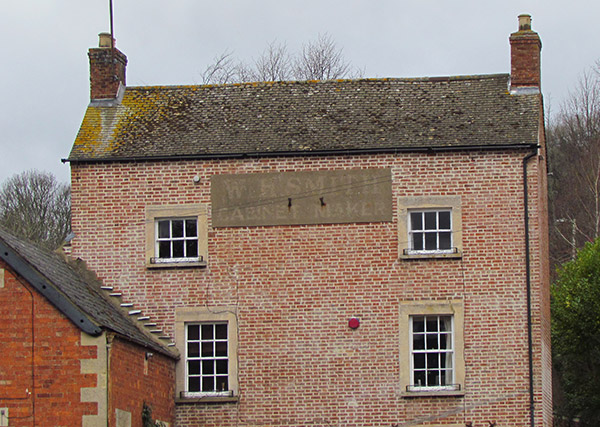 A close up of a Georgian double fronted house which carries an old sign saying 'WR SMITH CABINET MAKER'.