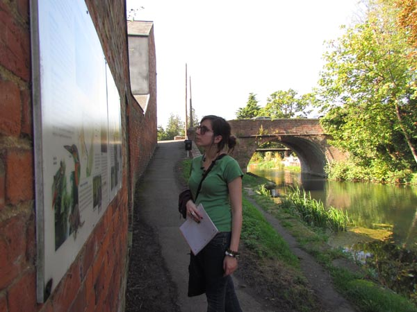 A girl looks at some panels next to the towpath at Ryeford Wharf.