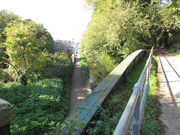 Seen from the top of the bridge, the low level riveted iron bridge parapet can be picked out and a view down the towpath to the left and along the railway path to the right are possible.