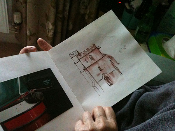 A watercolour book is held open and on the right hand page is a watercolour sketch of the church tower.