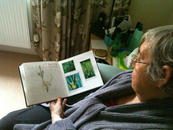 Iris sits in a chair looking at pages of her sketch book.