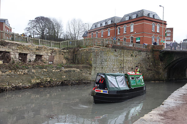 A small boat, with a green canopy, moves along the canal.