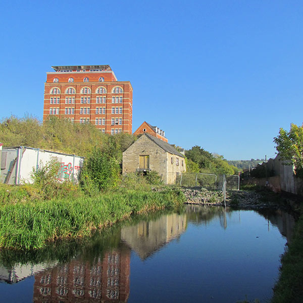 Hill Paul is an impressive red brick building. In this photo, the bright blue sky is reflected in the canal.